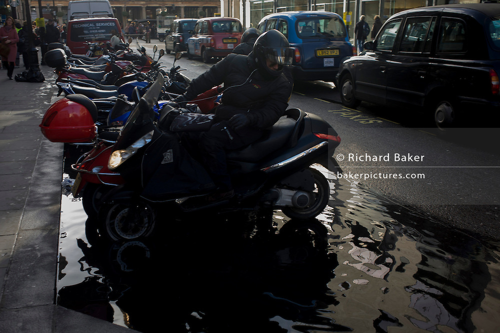 A scooter rider looks back at the depth of flooded water after recent showers of a parking space near Covent Garden in central London.