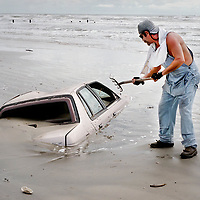 A mand tries to dig out a car with pitch fork after Tropical Storm Francis flooded the coastal area.    (Photo by Kim Christensen)