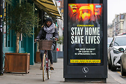 © Licensed to London News Pictures. 10/01/2021. London, UK. A cyclist without wearing a protective face covering rides past the Government's 'Stay Home, Save Lives' Covid-19 publicity campaign poster in north London, as the number of cases of the mutated variant of the SARS-Cov-2 virus continues to spread around the country. The message in the advertising campaign poster says 'The new variant of Covid-19 is spreading fast'. <br /> Almost 60,000 new cases of coronavirus were reported in the UK on Saturday 9 January 2021 and the number of deaths after a positive test passed 80,000, since the pandemic began. Photo credit: Dinendra Haria/LNP