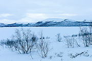 Frozen Kilpisjarvi lake with Sweden in the background in arctic wilderness at nightfall by Kilpisjarvi, Finland