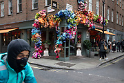 Flowers adorn the exterior of Bills restaurant on the ocrner of Brewer Street and Lexington Street in Soho on 18th February 2020 in London, England, United Kingdom. People pass this colourful and vibrant makeover of the famous restaurant chain.