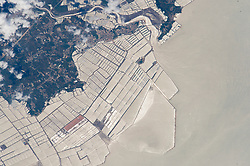 An astronaut aboard the International Space Station focused near the Sun's reflection point to shoot this photograph of grid-patterned fish farms on the coast of China's northeast province of Liaoning. The aquaculture basins have been built out from the wooded coast to a distance of nearly 6 kilometers (4 miles). Fish farms have been constructed at many points along the provincial coastline, but this group of basins facing the Yellow Sea is the largest. (Liaoning Province is the sixth in China in terms of aquaculture production.)<br /> The basins are built on shallow seabeds, mudflats, and bays.<br /> Islands, such as the one at image center, often help anchor the construction of basins. Outer barriers protect the basins from winter storms. Water flow lines and a ship wake are visible near the river estuary.<br /> Most aquaculture products are marketed live in China, with less than 5 percent processed for local or overseas markets.<br /> Shellfish, a traditional marine food source, still dominates the marine species production (77 percent), with sea fish a distant second (5 percent).<br /> About 4.3 million people are involved in freshwater and marine fish production in China (as of 2007).<br /> Click here to view another high-contrast astronaut photograph of fish farms near the Nile Delta.<br /> Astronaut photograph ISS044-E-89407 was acquired on September 6, 2015, with a Nikon D4 digital camera using an 1150 millimeter lens, and is provided by the ISS Crew Earth Observations Facility and the Earth Science and Remote Sensing Unit, Johnson Space Center. The image was taken by a member of the Expedition 44 crew. The image has been cropped and enhanced to improve contrast, and lens artifacts have been removed. The International Space Station Program supports the laboratory as part of the ISS National Lab to help astronauts take pictures of Earth that will be of the greatest value to scientists and the public, and to make those images freely available on the Internet. 
