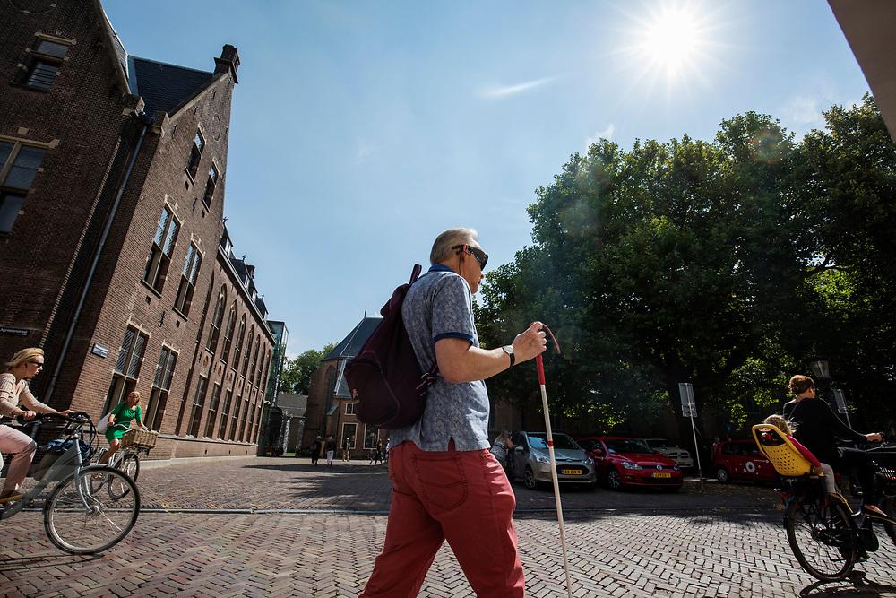 In Utrecht loopt een man met een blindegeleidenstok door de binnenstad.<br /> <br /> In Utrecht a blind man walks in the city center.