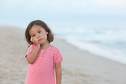 little girl with hand on her face at the beach