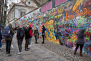 """The John Lennon Memorial Wall in Velkoprevorske namesti(Grand Priory Square), Malá Strana, on 18th March, 2018, in Prague, the Czech Republic. The Lennon Wall or John Lennon Wall is a wall in Prague, Czech Republic. Once a normal wall, since the 1980s it has been filled with John Lennon-inspired graffiti and pieces of lyrics from Beatles' songs. In 1988, the wall was a source of irritation for the communist regime of Gustáv Husák. Young Czechs would write grievances on the wall and in a report of the time this led to a clash between hundreds of students and security police on the nearby Charles Bridge. The movement these students followed was described ironically as """"Lennonism"""" and Czech authorities described these people variously as alcoholics, mentally deranged, sociopathic, and agents of Western capitalism."""