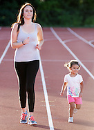 Karen Price runs with her daughter Gianna Price, 2, during the Twilight Track Series at Middletown High School on Tuesday, July 30, 2013.