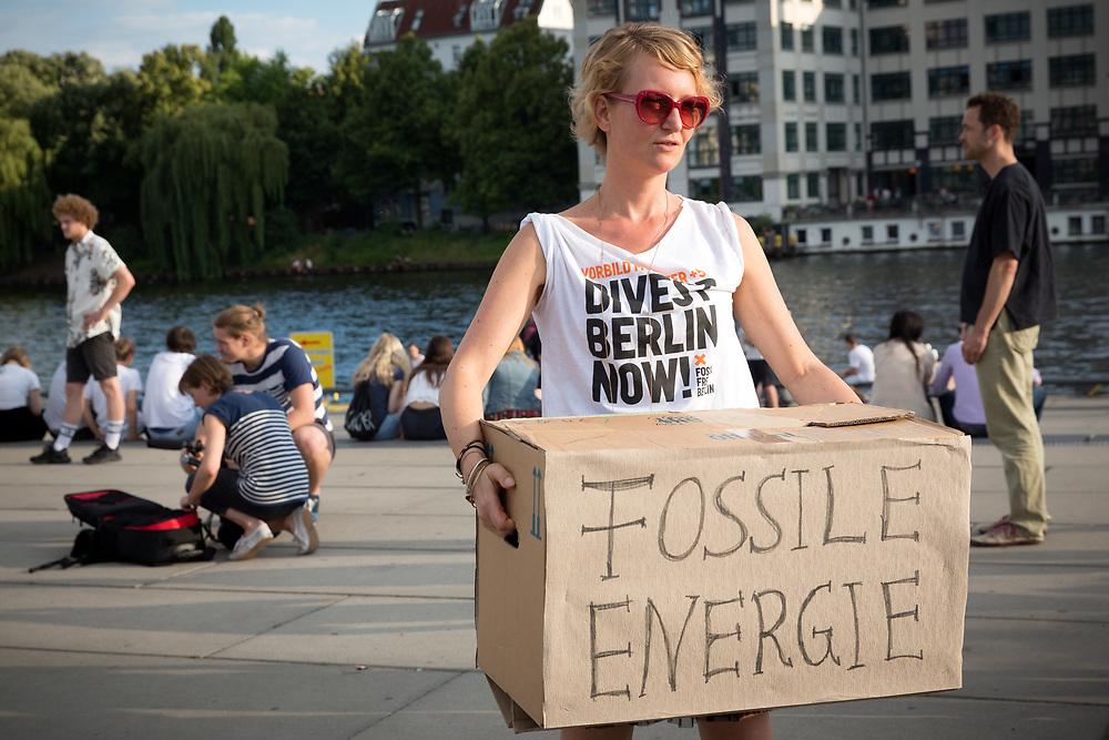 """Aktivisten von Fossil Free Berlin reissen symbolisch eine """"Mauer der fossilen Energie"""" an der East Side Gallery in Berlin ein. Seit Jahren kaempft die Initiative für den Abzug der öeffentlichen Investition aus Unternehmen des fossilen Brennstoffsektors. Am folgenden Tag beschliesst das Berliner Abgeordnetenhaus mit Stimmen aller fuenf Fraktionen, oeffentliche Gelder aus Unternehmen, deren Geschaeftsmodell dem Ziel der Klimaneutralitaet widerspricht innerhalb der naechsten fuenf Jahre abzuziehen. <br /> <br /> [© Christian Mang - Veroeffentlichung nur gg. Honorar (zzgl. MwSt.), Urhebervermerk und Beleg. Nur für redaktionelle Nutzung - Publication only with licence fee payment, copyright notice and voucher copy. For editorial use only - No model release. No property release. Kontakt: mail@christianmang.com.]"""