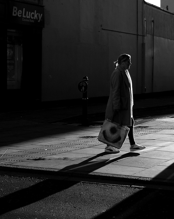 A lady walks through the high street in Cheltenham, England with a shopping bag during the Covid-19 pandemic on Friday 27th November 2020