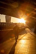 Man walking under Cannon Street Railway Bridge at sunrise, London, England, UK