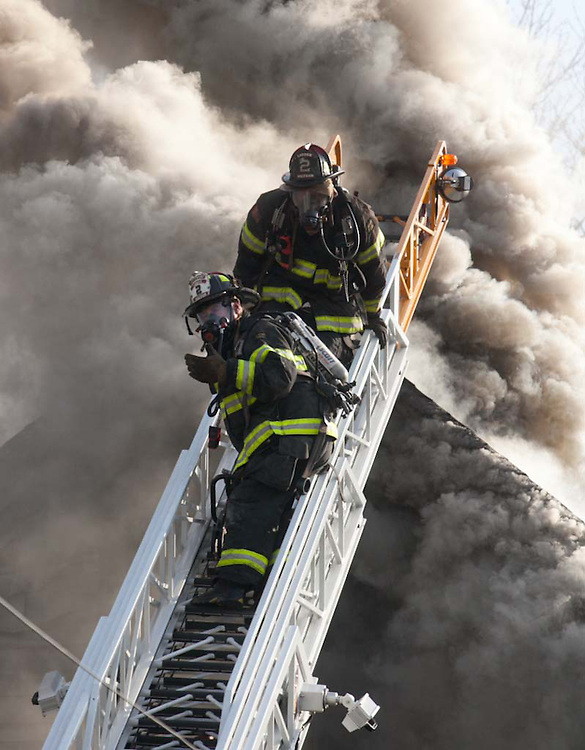 Waltham, MA 02/18/2012<br /> Firefighters from Waltham Ladder 2 retreat from the roof while fighting a 3 alarm fire that consumed the home of local business owner Wayne Brasco on Saturday afternoon.