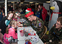 Brienna Ricker watches as Madelyn Lounsbury gets her face painted by Riley Woods of the Civil Air Patrol in Santa's Workshop during the annual Christmas Village on Thursday evening.   (Karen Bobotas/for the Laconia Daily Sun)