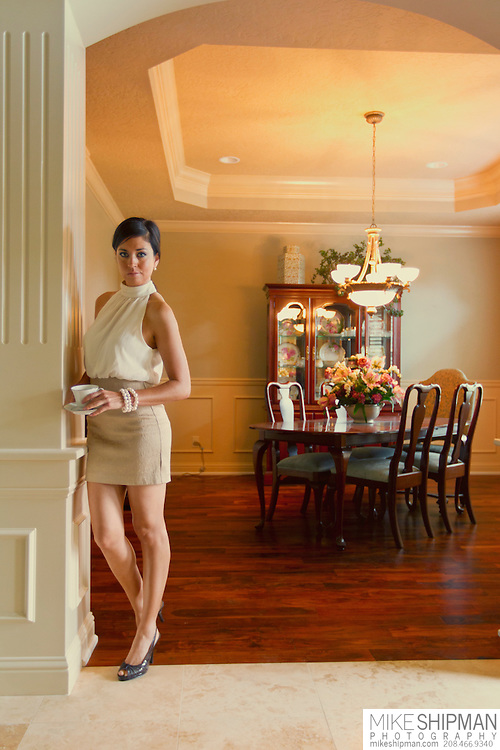Young brunette woman in a tan skirt and white blouse leans against a square column in the entryway of a formal dining room, holding a tea cup. MR.