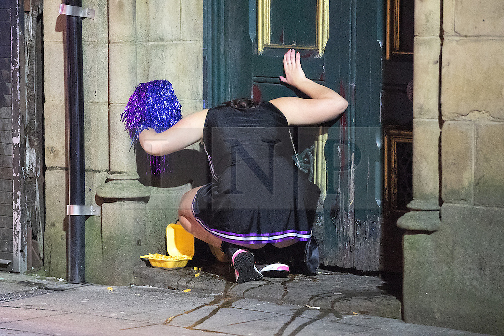© Licensed to London News Pictures . 27/12/2016 . Wigan , UK . A woman in sick in a doorway . Revellers in Wigan enjoy Boxing Day drinks and clubbing in Wigan Wallgate . In recent years a tradition has been established in which people go out wearing fancy-dress costumes on Boxing Day night . Photo credit : Joel Goodman/LNP