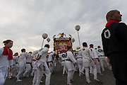 Mikoshi are carried onto Southern Beach at dawn during the Hamaorisai matsuri in Chigasaki, Kanagawa, Japan. Monday July 17th 2017.  This festival is celebrated on Marine Day in Japan. Over 40 mikoshi (portable shrines) are paraded through the night to arrive on the coast at Southern Beach where they are blessed in a Shinto ritual before being carried into the waves to be purified.