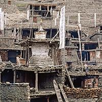 Manang Valley, Nepal. Prayer flags hang outside a shrine among houses in Manang village.