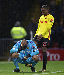Watford goalkeeper Heurelho Gomes holds his head after a collision as team-mate Christian Kabasele checks on his condition during the Premier League match at Vicarage Road, Watford.