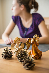 Decorative Christmas angel figurines with musical instruments and pine cones in front of teenage girl, Bavaria, Germany