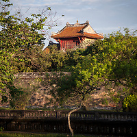 The rooftop of the top tier of the Hien Lam Pavilion (Hiển Lâm Các) can be seen over the inner wall of that surrounds the Imperial City in Hue, Vietnam.