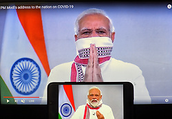 April 14, 2020, Kolkata, India: Indian Prime Minister Narendra Modi seen on a smartphone and screen announcing extension of the lockdown up to 3rd May as a preventive measure against the spread of Coronavirus..India has confirmed 10,200 coronavirus cases and 330 deaths. (Credit Image: © Avishek Das/SOPA Images via ZUMA Wire)
