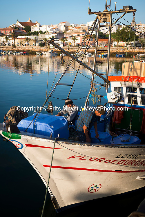 Lagos, Algarve, Portugal, June 2014. Fishermen arrive early in the morning with the catch of the day in the port of Lagos. A spectacular coastline of steep sandstone cliffs borders hidden sandy beaches on the south western tip of Europe, where the Mediterranean becomes the Atlantic Ocean.  Photo by Frits Meyst / MeystPhoto.com