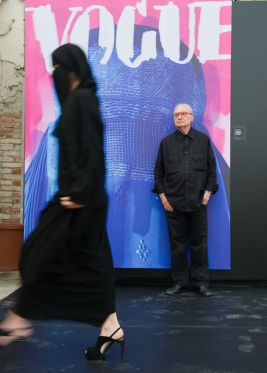 """VENICE, ITALY - JUNE 01:  Creator of fashion magazines and artist Flavio Lucchini poses with a model in front of his work """"poster/vogue"""" part of the exhibition """"What Women Want (?)"""" on June 1, 2011 in Venice, Italy. The exhibition addresses the controversiat theme of the burqa"""