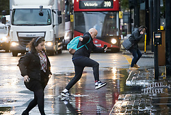 © Licensed to London News Pictures. 21/10/2021. London, UK. A commuter leaps over flood water on the Euston road in North London caused by heavy rain over night in the capital. Flash flooding hit parts of the south east as Storm Aurore brought winds of up to 45mph . Photo credit: Ben Cawthra/LNP