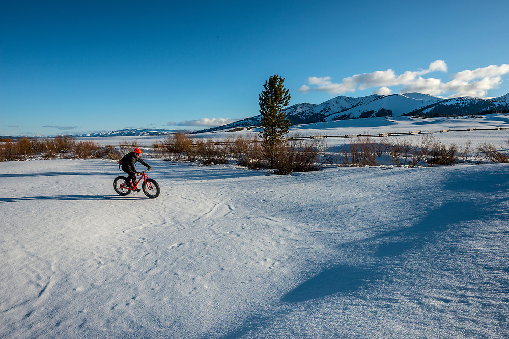 Spring freeze thaw makes for rock hard morning surface on Sawtooth Valley snow pack in Central Idaho for Snow Biking without stay on a groomed trail.  Licensing and Open Edition Prints.