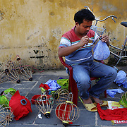 A man makes lanterns on a street corner in Hoi An, Vietnam. Hoi An is an ancient town and an exceptionally well-preserved example of a South-East Asian trading port dating from the 15th century. Hoi An is now a major tourist attraction because of its history. Hoi An, Vietnam. 5th March 2012. Photo Tim Clayton