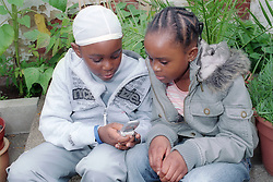 Young girl watching brother texting on his mobile phone,