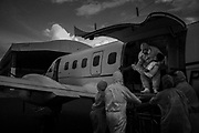 Under the rain, health professionals remove a 10-year-old patient in bad conditions due to Covid-19 from the plane of the Aerial Intensive Care Unit (ICU) of the State of Amazonas that carried out his transfer from Santo Antônio do Içá (879 km in a straight line from Manaus) to Eduardo Gomes Airport in Manaus, Amazonas, Brazil, on May 22, 2020. Upon arrival, the patient was received by other health professionals in an ambulance and was transferred to the Delphina Aziz Hospital, which only treated cases of the new coronavirus. The interior of the state of Amazonas surpassed the capital in the number of cases. Of the almost 200 thousand cases of the disease in the widest state of Brazil, approximately 60% are from the municipalities of the countryside.