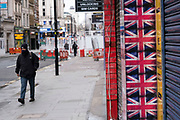 Man wearing a face mask walks past shuttered closed shops covered with Union Jack flags along the shopping district Oxford Street which is largely empty of shoppers as the national coronavirus lockdown three continues on 28th January 2021 in London, United Kingdom. Following the surge in cases over the Winter including a new UK variant of Covid-19, this nationwide lockdown advises all citizens to follow the message to stay at home, protect the NHS and save lives.
