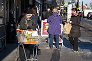 With most non-essential shops now closed and with retail sales suffering due to the Coronavirus pandemic, shoppers wearing face masks and face shields at Sainsburys supermarket out shopping on Kings Heath High Street on 31st December 2020 in Birmingham, United Kingdom. Small businesses have struggled through the Covid-19 pandemic and many have closed down altogether, while the big supermarkets have thrived, as the recession in the economy deepens and the crisis continues.