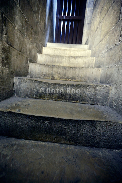 steps of narrow stairs with gate at the end
