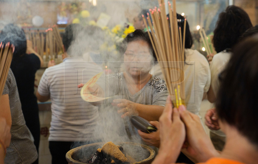 © Licensed to London News Pictures. 24 Ipoh, Malaysia. Devotees pray at the Tow Boo Keong Temple in Ipoh, Malaysia during the first day of the Nine Emperor Gods Festival,  Wednesday, Sept. 24, 2014. The festival is a nine-day Taoist celebration to mark the birth of the Nine Emperor Gods from the first day to the ninth day of the ninth moon in Chinese Lunar Calender. The origin of the Nine Emperor Gods (stars of the Northern constellation) can be traced back to the Taoist worship of the Northern constellation during Qin and Han Dynasty and absorb this practice of worshipping the stars and began to deitify them as Gods. During the festival devotees are to remain celibate, female devotees who are menstruating are advised to keep away from praying to the Nine Emperor Gods and vegetarian diet is strictly observed during the entire nine days. Photo credit : Sang Tan/LNP