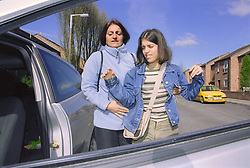 Teenage girl with physical disability preparing to climb into car with assistance of her mother,