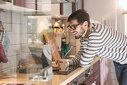 Man with laptop and cup in the kitchen, Munich, Germany