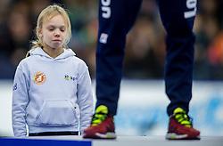 10-12-2016 NED: ISU World Cup Speed Skating, Heerenveen<br /> 1500 m men / ceremonie begeleidster kijkt naar Wereldkampioen Denis Yuskov uit Rusland eindigde op de tweede plaats (1.45,41).