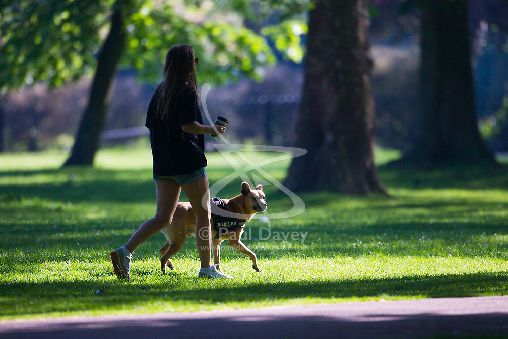 As the working week begins following the hottest May Bank Holiday on record, a woman and her dog enjoy the early morning sunshine in North West London's Queen's Park. London, May 08 2018.