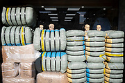 The hads of female mannequins peer over the wrapped products that have been imported from China, sen in a clothing business on the Commercial Road in the East End, on 21st October 2021, in London, England.