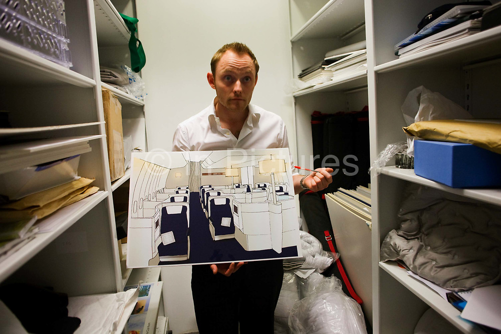 """In an office stock room, an archivist in British Airways' Customer Experiences Divition shows some conceptual design ideas for future Business Class cabin layouts, seen at the airline's corporate headquarters at Waterside at Harmondsworth near Heathrow Airport. Having listened to their passengers' ideas for what they'd like to experience in their long-haul cabins, BA regularly come up with ways to make the flight for premium users a reason to become loyal fare-payers. From writer Alain de Botton's book project """"A Week at the Airport: A Heathrow Diary"""" (2009). .."""