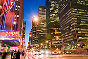 Radio City Music Hall in Manhattan, New York City, at night, with Rockefeller Center office buildings and traffic on Avenue of the Americas.