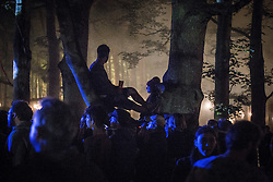 © Licensed to London News Pictures . 22/07/2013 . Suffolk , UK . A man and a woman sit in the trees in the forest of Henham Park as others dance around them . Revellers enjoy the final night of the Latitude Festival . The Latitude music and culture festival in Henham Park , Southwold . Photo credit : Joel Goodman/LNP
