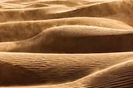 Windswept desert sand dunes at Erg Lihoudi, Morocco.