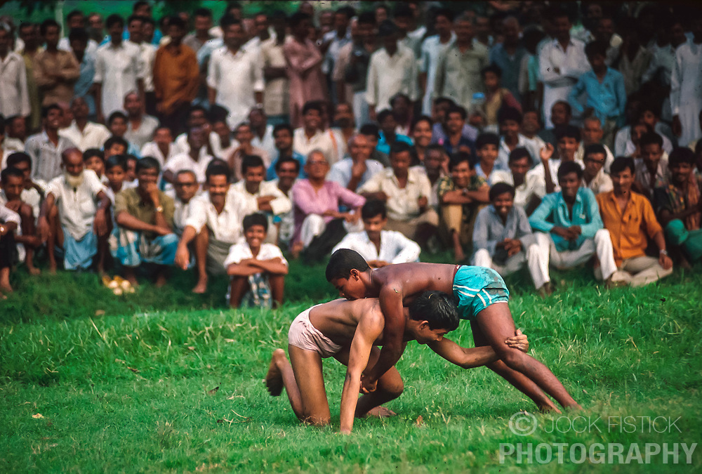 CALCUTTA, INDIA - OCTOBER 1992 - A crowd gathers for an impromptu wrestling match. Most city dwellers can not afford the price of a ticket to watch a crickett match in the stadium, so they make their own fun, and wager on the participants. .(PHOTO © JOCK FISTICK)
