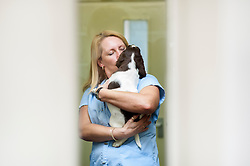 Puppy dog gets a hug from a veterinary nurse, Arnwood Veterinary Surgery, Nottingham, England, UK.