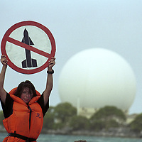 Female activist ( Anne Marie Rasmussen) in life vest holding up sign with red stripe through missile, Kwajalein radar dome visible in back.