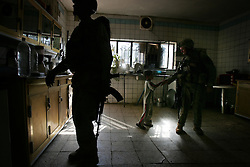 An Iraqi soldiers searches kitchen cabinets while an American soldier makes friends in the Baghdad Sunni neighborhood of Ghazaliyah. The search - part of an operation by bolstered US and Iraqi forces in the hopes of getting a handle on the extraordinary numbers of sectarian killings in Baghdad - was carried out by the recently extended Alaska-based 4BN 23rd Infantry Regiment of the 172nd Stryker Brigade - Baghdad, Iraq on Tuesday August 15, 2006. The brigade, which was in the process of rotating home at the end of a year tour in Mosul and northwestern Iraq, was diverted to the capital for an undetermined number of additional months.