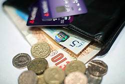 File photo dated 29/1/2017 of Coins and a five pound and ten pound banknotes and cards in a wallet. The International Monetary Fund (IMF) has downgraded its growth forecast for the UK after weaker-than-expected economic performance.