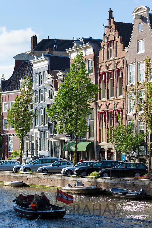 Tourists on canal boat trip passing Johannes Restaurant on canalside street in famous Herengracht in Amsterdam, Holland