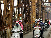 23 DECEMBER 2017 - HANOI, VIETNAM: Traffic on the Long Bien Bridge. Long Biên Bridge is a historic cantilever bridge across the Red River that connects two districts, Hoan Kiem and Long Bien of the city of Hanoi, Vietnam. It was originally called Paul Doumer Bridge. The bridge was built in 1899-1902 by the architects Daydé & Pillé of Paris, and opened in 1903. Before North Vietnam's independence in 1954, it was called Paul-Doumer Bridge, named after Paul Doumer - The Governor-General of French Indochina and then French president. At 1.68 kilometres (1.04 mi) in length, it was, at that time, one of the longest bridges in Asia. For the French colonial government, the construction was of strategic importance in securing control of northern Vietnam. From 1899 to 1902, more than 3,000 Vietnamese took part in the construction.    PHOTO BY JACK KURTZ
